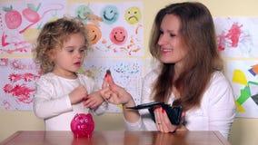 Ευτυχείς μητέρα και κόρη που βάζουν τα νομίσματα στη piggy τράπεζα φιλμ μικρού μήκους