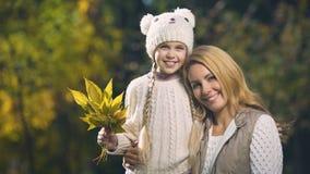 Ευτυχείς μητέρα και κόρη που χαμογελούν και που εξετάζουν τη κάμερα, κέντρο υιοθέτησης, πτώση απόθεμα βίντεο