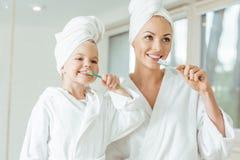 ευτυχείς μητέρα και κόρη στο βούρτσισμα μπουρνουζιών και πετσετών στοκ εικόνες με δικαίωμα ελεύθερης χρήσης
