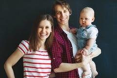 Ευτυχείς μητέρα οικογενειακών πατέρων και γιος μωρών στο μαύρο υπόβαθρο στοκ εικόνες με δικαίωμα ελεύθερης χρήσης