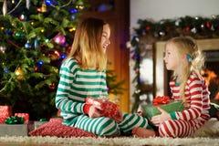 Ευτυχείς μικρές αδελφές που φορούν τις πυτζάμες Χριστουγέννων που παίζουν από μια εστία σε ένα άνετο σκοτεινό καθιστικό στη Παραμ στοκ φωτογραφίες με δικαίωμα ελεύθερης χρήσης