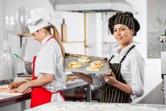 Ευτυχείς μικρές πίτσες εκμετάλλευσης αρχιμαγείρων στο δίσκο στην κουζίνα στοκ εικόνες