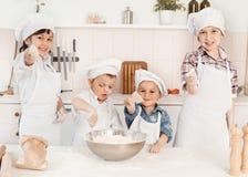 Ευτυχείς μικροί αρχιμάγειρες που προετοιμάζουν τη ζύμη στην κουζίνα Στοκ φωτογραφία με δικαίωμα ελεύθερης χρήσης