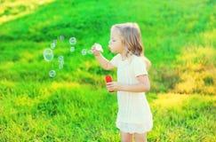 Ευτυχείς μικρών κοριτσιών φυσαλίδες σαπουνιών παιδιών φυσώντας το καλοκαίρι στοκ φωτογραφίες με δικαίωμα ελεύθερης χρήσης