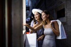 Ευτυχείς νέες γυναίκες με τις τσάντες αγορών που απολαμβάνουν στις αγορές Καταναλωτισμός, αγορές, έννοια τρόπου ζωής στοκ φωτογραφία