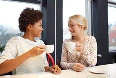 Ευτυχείς νέες γυναίκες που πίνουν το τσάι ή τον καφέ στον καφέ Στοκ Εικόνα