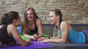 Ευτυχείς νέες φίλαθλοι που γελούν χαρωπά χαλαρώνοντας μετά από να ασκήσει απόθεμα βίντεο