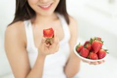 Ευτυχείς νέες φράουλες εκμετάλλευσης χαμόγελου γυναικών στοκ φωτογραφία με δικαίωμα ελεύθερης χρήσης