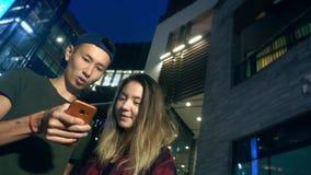 Ευτυχείς νέοι ασιατικοί φίλος και φίλη ζευγών χρησιμοποιήστε ένα smartphone στεμένος σε μια οδό πόλεων το βράδυ απόθεμα βίντεο