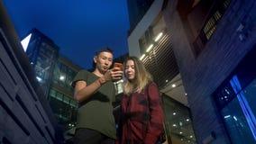 Ευτυχείς νέοι ασιατικοί φίλος και φίλη ζευγών χρησιμοποιήστε ένα smartphone στεμένος σε μια οδό πόλεων το βράδυ φιλμ μικρού μήκους