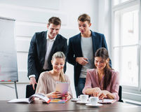 Ευτυχείς νέοι επιχειρηματίες που χρησιμοποιούν το PC ταμπλετών στο γραφείο στην αρχή Στοκ εικόνες με δικαίωμα ελεύθερης χρήσης