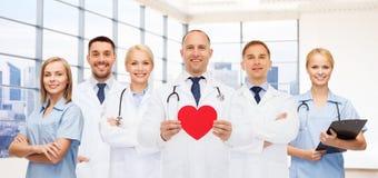 Ευτυχείς νέοι καρδιολόγοι γιατρών με την κόκκινη καρδιά στοκ εικόνα με δικαίωμα ελεύθερης χρήσης