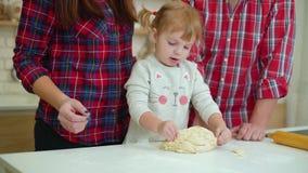 Ευτυχείς νέοι με το κορίτσι μικρών παιδιών που έχει τη διασκέδαση που μαγειρεύει από κοινού απόθεμα βίντεο