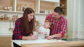 Ευτυχείς νέοι με το κορίτσι μικρών παιδιών που έχει τη διασκέδαση με το αλεύρι στην κουζίνα απόθεμα βίντεο