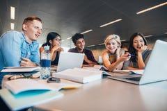 Ευτυχείς νέοι που κάνουν τη μελέτη ομάδας στη βιβλιοθήκη Στοκ Φωτογραφίες