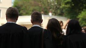 Ευτυχείς νέοι που πετούν τα ακαδημαϊκά καπέλα επάνω στον αέρα, βαθμολόγηση εορτασμού φιλμ μικρού μήκους