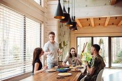 Ευτυχείς νέοι που τρώνε και που δίνουν τις φρυγανιές στην κουζίνα Στοκ Εικόνες