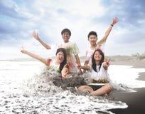 Ευτυχείς νέοι σε μια παραλία το καλοκαίρι με τη σε αργή κίνηση και μουτζουρωμένη έννοια Στοκ φωτογραφία με δικαίωμα ελεύθερης χρήσης