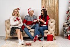 Ευτυχείς νέοι στα πουλόβερ και καπέλα santa που κάθονται στον καναπέ στοκ εικόνα