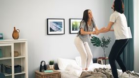 Ευτυχείς νέοι στις πυτζάμες που χορεύουν στο κρεβάτι στο σπίτι που έχει τη διασκέδαση από κοινού φιλμ μικρού μήκους
