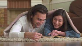 Ευτυχείς νέοι τύπος και κορίτσι που βρίσκονται στον τάπητα στο πάτωμα και που διαβάζουν ένα βιβλίο απόθεμα βίντεο