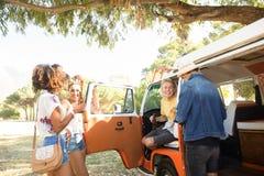 Ευτυχείς νέοι φίλοι που υπερασπίζονται το φορτηγό τροχόσπιτων στη θέση για κατασκήνωση στοκ εικόνες