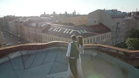 Ευτυχείς νέοι όμορφοι μοντέρνοι νύφη και νεόνυμφος ζευγών που αγκαλιάζουν ήπια στη στέγη στην οδό πόλεων ηλιοβασιλέματος στο υπόβ απόθεμα βίντεο