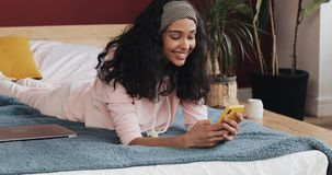 Ευτυχείς να κουβεντιάσει και αποστολή κειμενικών μηνυμάτων κοριτσιών αφροαμερικάνων στο smartphone που βρίσκονται στο κρεβάτι στο φιλμ μικρού μήκους