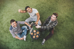 Ευτυχείς νεαροί άνδρες που πίνουν την μπύρα και που κάθονται στη χλόη ψήνοντας το κρέας στη σχάρα Στοκ φωτογραφία με δικαίωμα ελεύθερης χρήσης