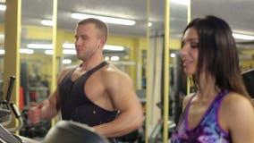 Ευτυχείς νεαρός άνδρας και γυναίκα που τρέχουν treadmill φιλμ μικρού μήκους