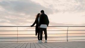 ευτυχείς νεολαίες αγά&pi Ζευγάρι που στέκεται στην ξύλινη αποβάθρα κοντά στη θάλασσα ή τον ωκεανό και που χαμογελά ο ένας στον άλ απόθεμα βίντεο