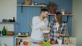 ευτυχείς νεολαίες κο&u Ελκυστικό άτομο που ταΐζει τη φίλη του ενώ μαγειρεύει το πρωί Στοκ Φωτογραφία