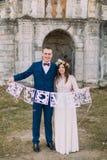 Ευτυχείς νύφη και νεόνυμφος που κρατούν τις καλλιτεχνικές επιστολές αγάπης papercut Στοκ Εικόνες