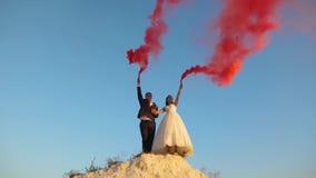 Ευτυχείς νύφη και νεόνυμφος που κυματίζουν το χρωματισμένο ρόδινο καπνό ενάντια στο μπλε ουρανό και το γέλιο honeymoon ρωμανικός  στοκ φωτογραφία με δικαίωμα ελεύθερης χρήσης
