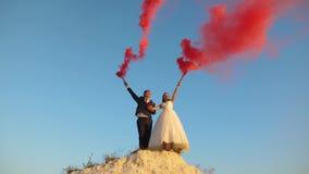 Ευτυχείς νύφη και νεόνυμφος που κυματίζουν το χρωματισμένο ρόδινο καπνό ενάντια στο μπλε ουρανό και το γέλιο honeymoon ρωμανικός  στοκ εικόνες