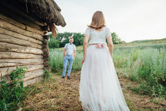 Ευτυχείς νύφη και νεόνυμφος που περπατούν στην πράσινη χλόη στοκ εικόνες