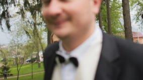 Ευτυχείς νύφη και νεόνυμφος που περπατούν στο πάρκο στη θερινή ημέρα Αγαπώντας γαμήλιο ζεύγος υπαίθριο γάμος νεόνυμφων εκκλησιών  φιλμ μικρού μήκους
