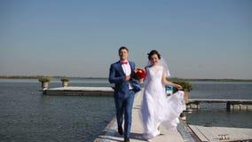 Ευτυχείς νύφη και νεόνυμφος που τρέχουν στο δρόμο τους πίσω απόθεμα βίντεο