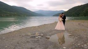 Ευτυχείς νύφη και νεόνυμφος στο υπόβαθρο ενός ποταμού Όμορφη αντανάκλαση των newlyweds στο νερό φιλμ μικρού μήκους
