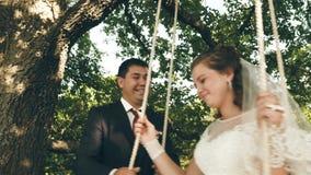 Ευτυχείς νύφη και νεόνυμφος στο όμορφο άσπρο φόρεμα που ταλαντεύεται στην ταλάντευση στο θερινό πάρκο ταλάντευση στον κλάδο μιας  απόθεμα βίντεο
