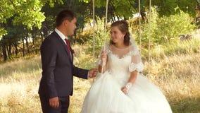 Ευτυχείς νύφη και νεόνυμφος στο όμορφο άσπρο φόρεμα που ταλαντεύεται στην ταλάντευση στο θερινό πάρκο ταλάντευση στον κλάδο μιας  φιλμ μικρού μήκους