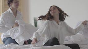 Ευτυχείς ξένοιαστοι άνδρας και γυναίκα που έχουν την πάλη μαξιλαριών χαράς διασκέδασης στο κρεβάτι που απολαμβάνει την αστεία δρα απόθεμα βίντεο