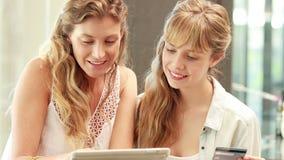 Ευτυχείς ξανθοί φίλοι που κάνουν on-line να ψωνίσει φιλμ μικρού μήκους