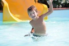 Ευτυχείς οδηγώντας φωτογραφικές διαφάνειες αγοριών παιδιών στο πάρκο aqua Στοκ Φωτογραφία