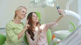Ευτυχείς οδοντίατρος και ασθενής που κάνουν selfie και που παρουσιάζουν β-σημάδι χαμόγελο γιατρών απόθεμα βίντεο