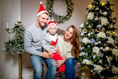 Ευτυχείς οικογένεια, πατέρας, μητέρα και γιος, το πρωί στο καθιστικό που διακοσμείται για τα Χριστούγεννα Ανοίγουν παρουσιάζουν κ στοκ φωτογραφίες