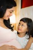Ευτυχείς οικογενειακές έγκυες μητέρα και κόρη στοκ φωτογραφία