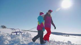 Ευτυχείς οικογενειακή μητέρα και κόρη παιδιών σε έναν χειμερινό περίπατο που υπαίθρια Όμορφη οικογένεια της απόλαυσης μητέρων και φιλμ μικρού μήκους