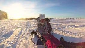 Ευτυχείς οικογενειακοί γύροι και χαμόγελο snowtube στους χιονώδεις δρόμους κίνηση αργή Χειμερινό τοπίο χιονιού Υπαίθρια αθλητισμό φιλμ μικρού μήκους