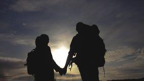 Ευτυχείς οικογενειακοί τουρίστες που περπατούν τη σκιαγραφία χεριών τρόπου ζωής εκμετάλλευσης στο ηλιοβασίλεμα έννοια ταξιδιού ομ απόθεμα βίντεο